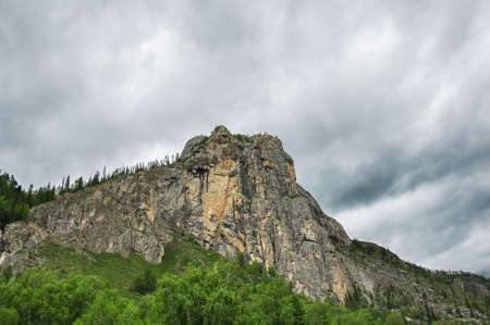The rock against heavy cloudy sky. Altai mountains, Russia. Stock Photo