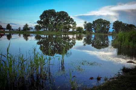 Sunset on the lake in evening twilght. Summer rural landscape Banque d'images