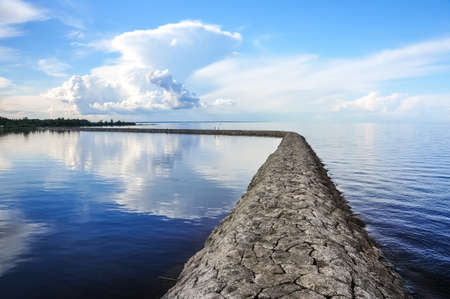 Stony dam quay on the Ladoga lake. Sunny summer landscape. Blue sky and clouds reflects in water surface Stock Photo