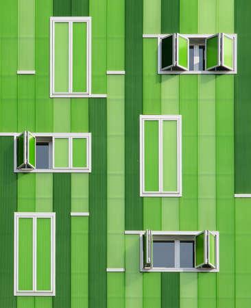 architectonic: Modern gebouw De groene gevel imiteren de textuur van bamboe met veel parallelle verticale lijnen van de ramen hebben verschillende maten Stockfoto