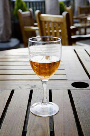 Glass of beer on a wooden table on an outdoor patio