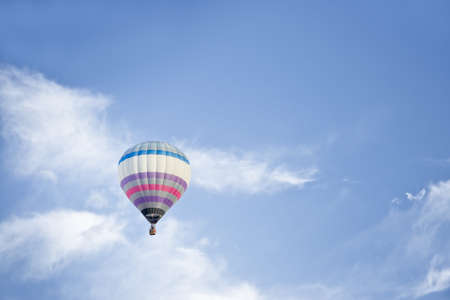 Multi colored Hot air Balloon isolated on a blue sky with white clouds photo