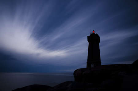 Lighthouse at night with red light and blue sky  photo