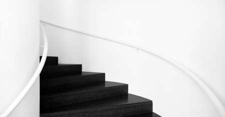 Spiral staircases between white walls and black floor Interior stairs in black and white photo