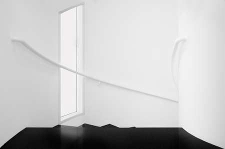 Spiral staircases between white walls and black floor Interior stairs in black and white
