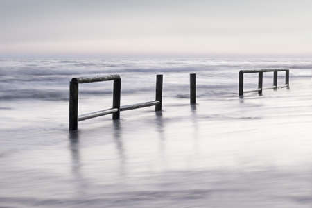 Wooden fence in sea water at dusk