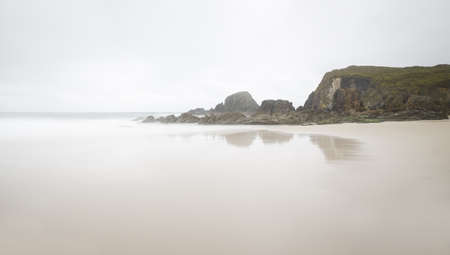 Spanich beach on a foggy day with some rocks. Picture for winter time, long exposure