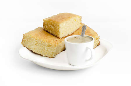 Sponge cake and a cup of coffe with milk on white background. Food on plate isolated