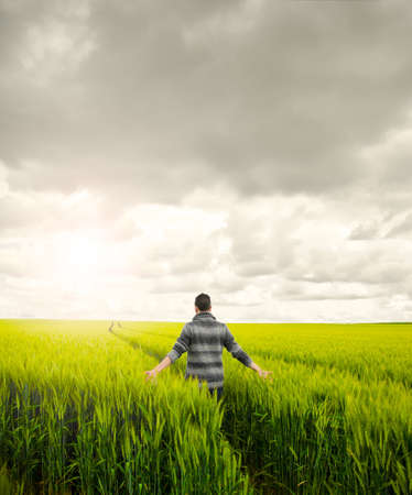 Man walking on a wheat field looking for a peace moment. Reaching relax and peace photo