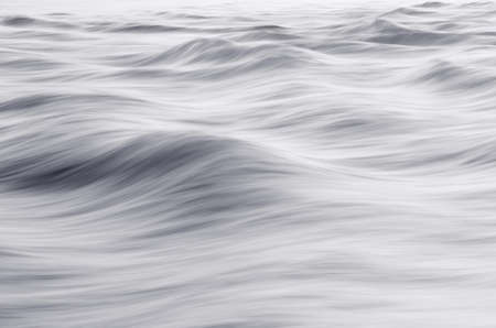 Water texture on silver. Sea background with small waves (long exposure). Closeup