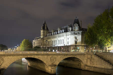 Seine River buildings. Seine River with beautiful buildings in the background at night, Paris Editorial
