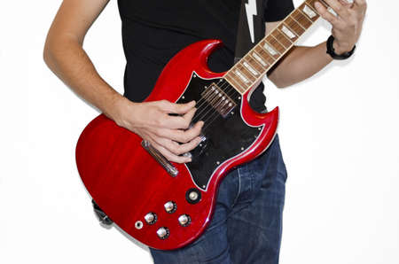 Playing the electrical guitar. Closeup view of playing electric  guitar. Young man playing his electrical red guitar on white background. photo