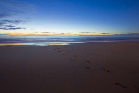 getting away from it all: Beach at dusk with footprints going towards the sea. Escape, getting away from it all, concept.  Stock Photo