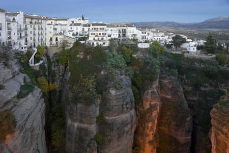 Typcal white spanish houses in Ronda, Malaga, Andalusia, over the scarped cliffs at dusk.