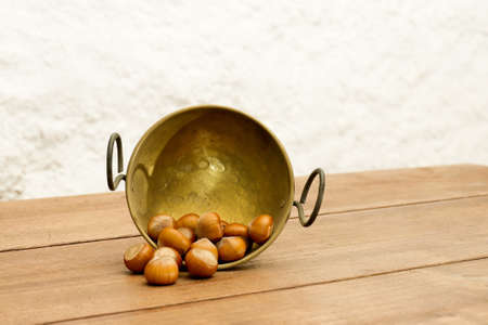 bronze bowl: Bowl of Chestnuts. Autumnal arrangement with a bronze bowl of chestnuts on wooden table