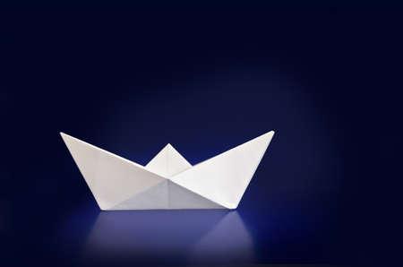 Paper boat. Origami paper boat on dark blue background