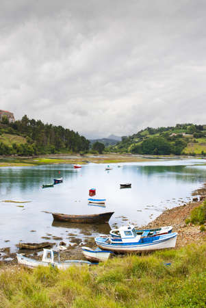 Fishing boats, low tide  Colorful, traditional fishing boats against the hills of San Vicente de la Barquera, village in Spain Stock Photo - 17284903