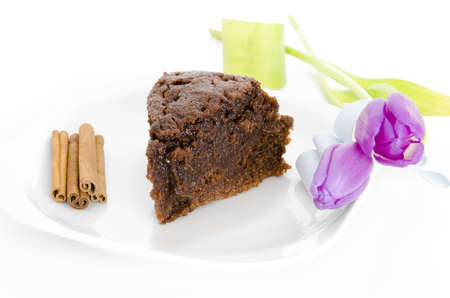 Chocolate cake. Piece of chocolate cake with cinnamon and tulip on white isolated background