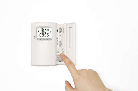Digital Thermostat. Digital Thermostat with a male hand. Adjusting and setting thermostat to save energy photo