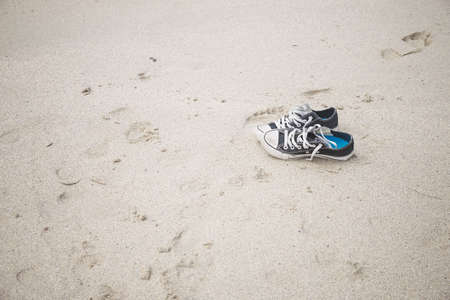Sneakers on the sand of the beach, summer time