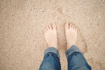 Woman legs and feet standing on the sand of the beach. Stock Photo