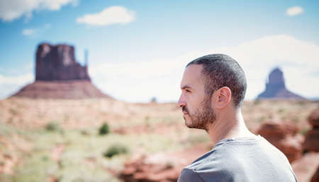 Man enjoying view of Monument Valley. Handsome young man looking outdoors, Arizona Utah, USA.