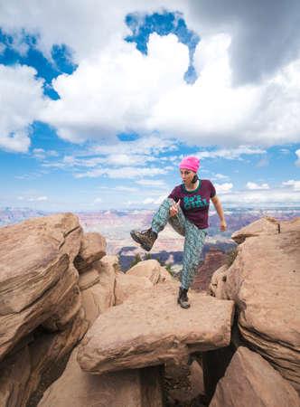 Happy girl joking in Grand Canyon. Young woman on hiking travel. Grand Canyon, south rim, Arizona, USA.