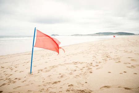 Warning sign of a red flag at a beautiful beach with a cloudy sky, Ferrol, Galicia, Spain, Europe