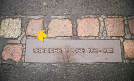12 NOVEMBER 2014 - BERLIN: Berlin wall sign in the road. The Berlin Wall, in German: Berliner Mauer was a barrier that divided Berlin from 1961 to 1989. Editorial