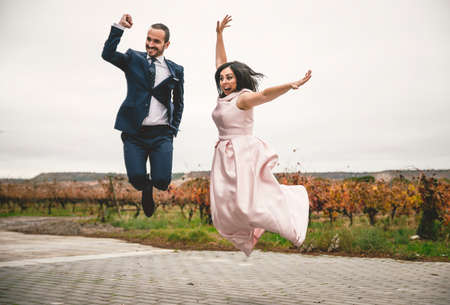 Happy bride and groom on their wedding jumping