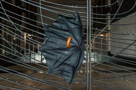 wind blown: Broken Wind Blown Damaged Umbrella on a fence