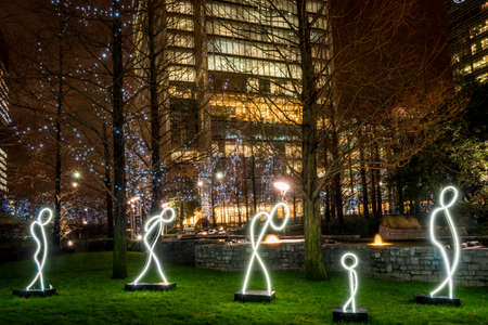 fleeing: London, United Kingdom - January 11, 2016: Winter Lights Festival at Canary Wharf, Docklands. My light is your light installation by Alaa Minawi. Installation is devoted to Syrian refugees, it shows silhouettes of six people, fleeing war and hoping for