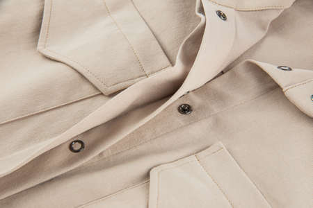 a fragment of a patch pocket with a flap and a button closure on a beige shirt made of thick cotton fabric Imagens