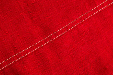 finishing stitch, double seam, made with beige threads in a product made of red linen fabric