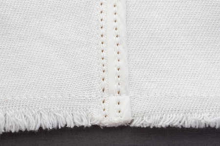 white denim fabric, connecting parts with various seams with brown threads, raw edge with fringe