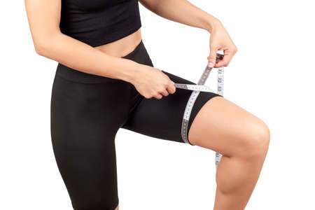 a young beautiful woman in a black tracksuit measures the volume of the thigh with a centimeter tape, isolate on a white background