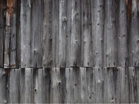 fragment of a fence made of old wooden boards with remnants of paint and nails, natural texture, background