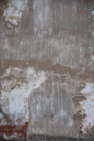 fragment of an old brick wall with concrete plaster and remnants of multicolored paint, grunge, background