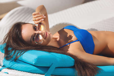 swimsuite: Beautiful girl laying on the blue lounger on the beach wearing sunglasses. Pretty woman near sea side in the swimsuite relaxing, having sunbath and tan. Looking at camera
