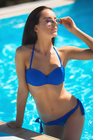 Beautiful girl standing in blue sweaming suite wearing the sunglasses in the pool