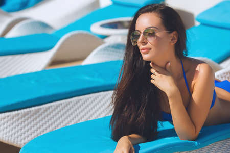 swimsuite: Beautiful girl laying on the blue lounger on the beach wearing sunglasses. Pretty woman near sea side in the swimsuite relaxing, having sunbath and tan. Stock Photo