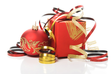 Red gift box with colorful ribbons and xmas baubles on white background