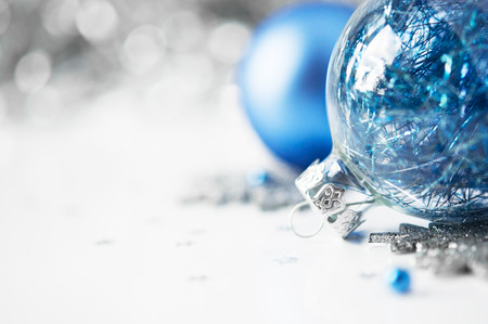 christmas decorations with white background: Blue and silver xmas ornaments on bright holiday background with space for text Stock Photo