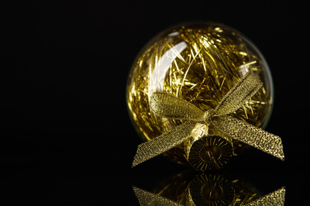 Golden xmas ball on black background with space for text