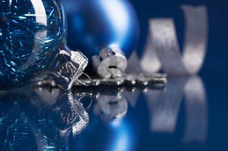 Blue and silver xmas ornaments on dark blue background with space for text