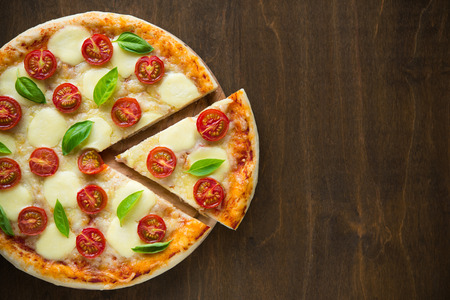 Pizza Margherita on dark wooden background top view Stock Photo