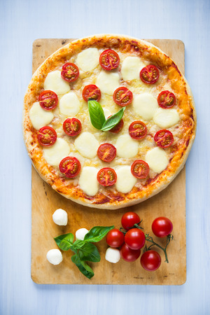 Pizza Margherita on blue background top view
