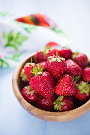 Wooden bowl filled with fresh ripe strawberries on an blue wooden textured table top Stock Photo