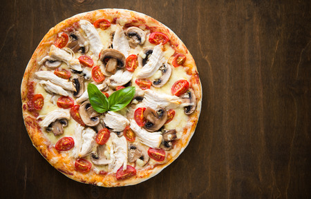 Pizza with chicken and mushrooms on dark wood background with space for text