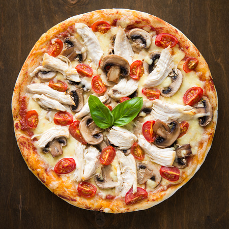 Pizza with chicken, tomato and mushrooms on dark background top view